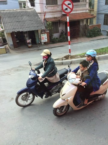 Mother and child riding a scooter into Hanoi