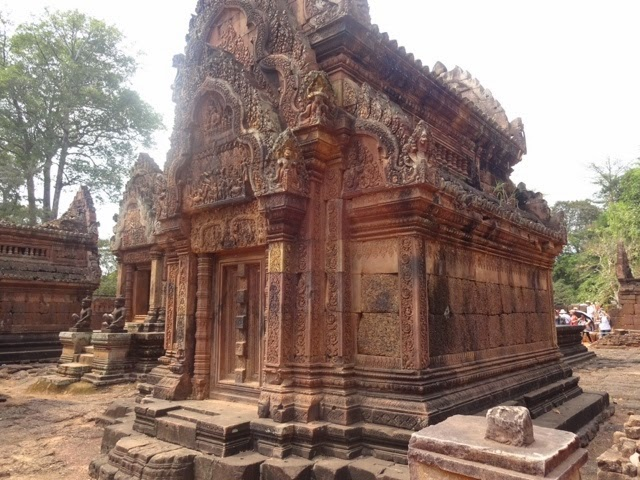 "The intricate facade of the Banteay Srei, or ""Lady Temple."" Even though the Banteay Srei was constructed in the late 10th century, earlier than Angkor Wat, the floral details have not yet faded. The temple was built by women, the decorations were carved by women, and only women were allowed to pray here, as reflected by the petite door-frames. Photograph by junior Snigdha Nandipati."